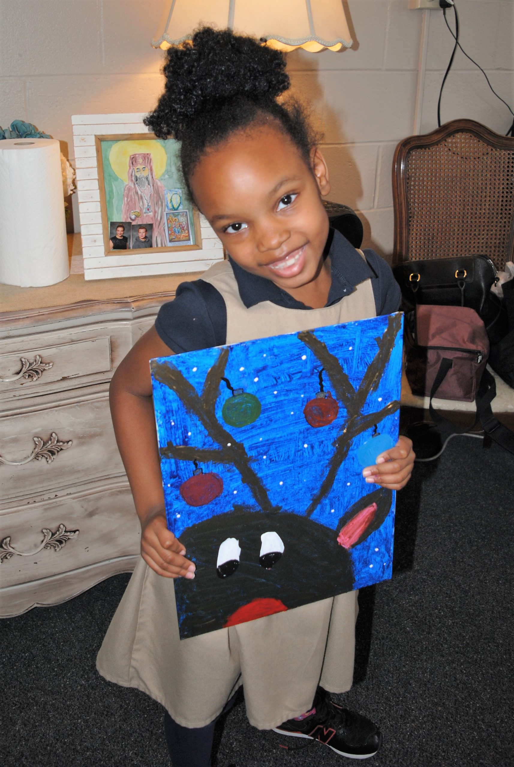 Student holds her hand-painted reindeer picture
